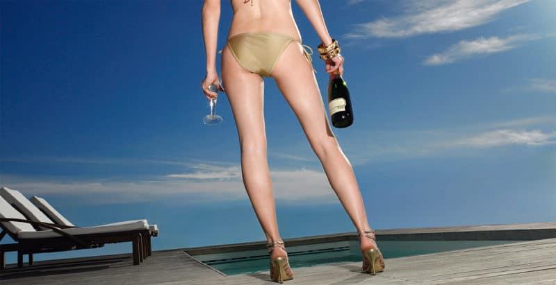 Dame mit sexy Beinen und Tan mit Champagner Flasche in der Hand
